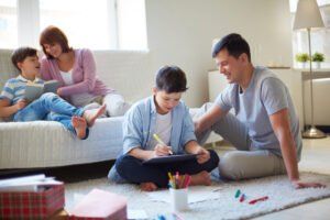 Happy parents practicing mindful parenting with kids helping them learn